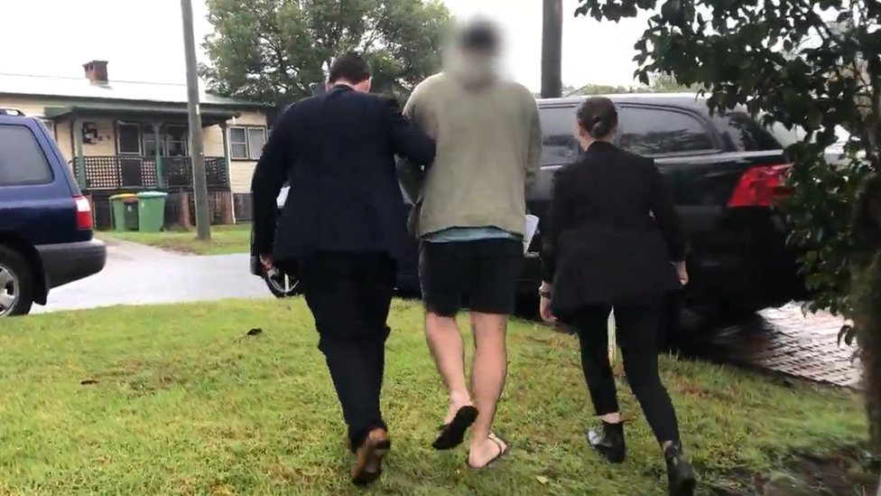 Detectives escorting the 30-year-old suspect in Wyong to police car