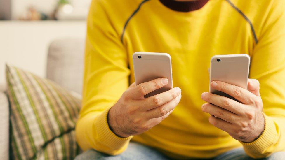 Hombre sosteniendo dos smartphones