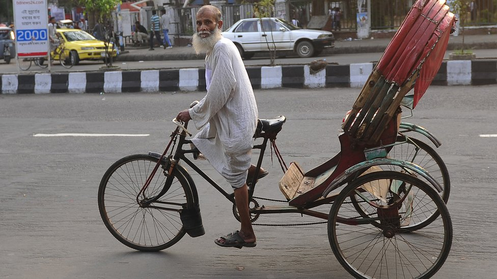 شخص مسن يدفع عجلة ركشا