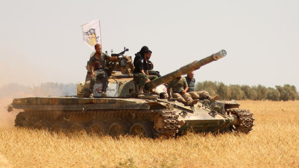 Rebel forces from Jaysh al-Islam (Army of Islam) stand on a tank as they hold a position on August 24, 2015 near the frontline in the al-Zahra area, on the northwestern outskirts of Aleppo
