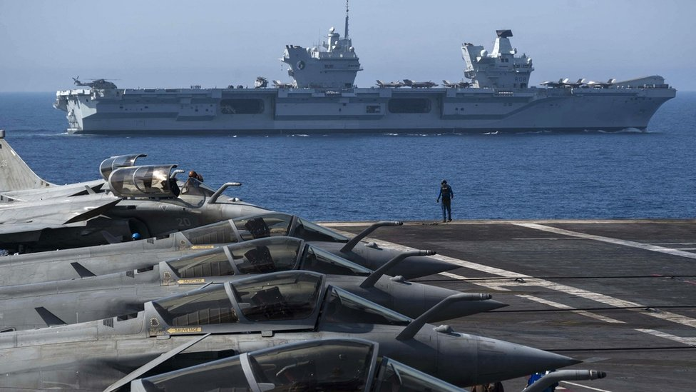 """French navy Rafale jet fighters sit on the bridge of the French aircraft carrier Charles de Gaulle with the UK Royal Navy's aircraft carrier HMS Queen Elizabeth in the background during the Navy exercise """"Gallic strike"""" off the coast of Toulon, south-eastern France on June 3, 2021."""