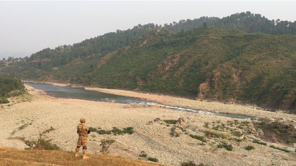 A soldier stands on the rocky shore of a river along the Kashmir Line of Control