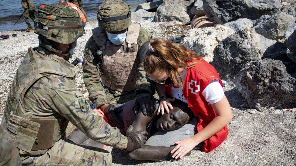 Una ayudante médica atendiendo a un migrante en la zona de Ceuta el 18 de mayo de 2021.