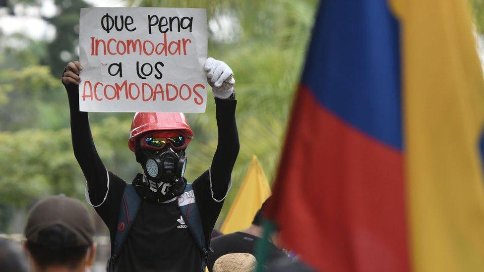 """""""Que pena incomodar a los acomodados"""", dice el cartel que sostiene un manifestante en las protestas que irrumpieron en mayo en Colombia."""