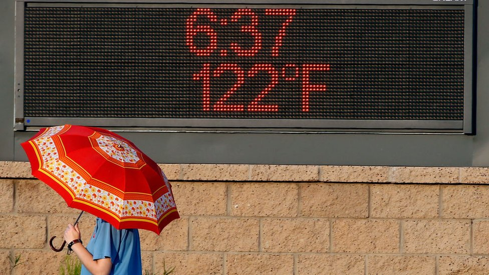 A pedestrian uses an umbrella to get some relief from the sun as she walks past a sign displaying the temperature on June 20, 2017 in Phoenix, Arizona