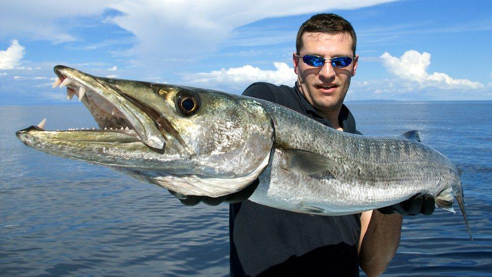 Hombre joven sostenniendo pez.