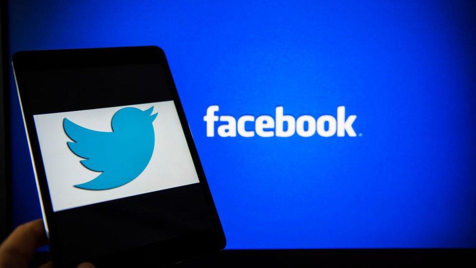 Logo de Twitter delante de un fondo con el logo de Facebook
