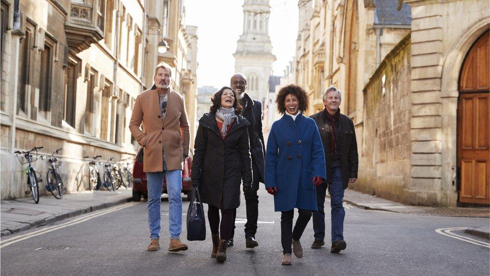Adultos caminando en grupo