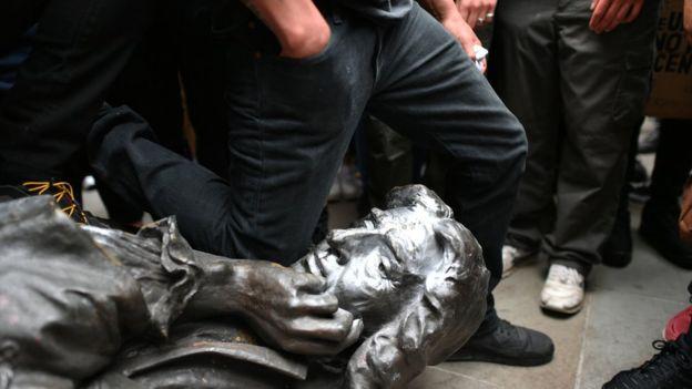 متظاهر يجثو على عنق تمثال كولستون البرونزي