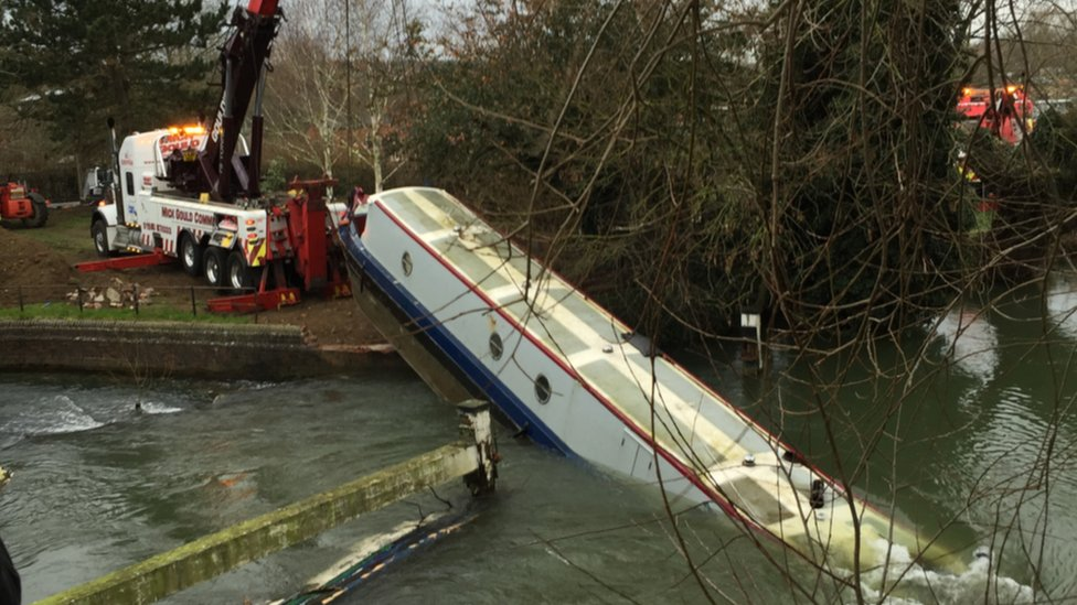 The Environment Agency using a winch attached to a crane to hoist the boat out of the water