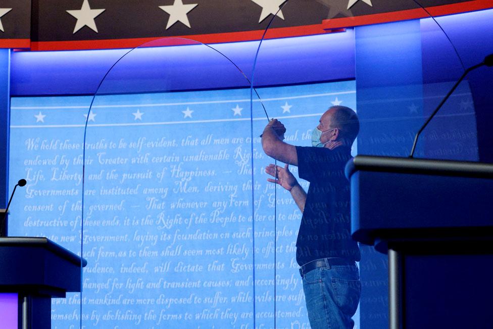 A worker adjusts plexiglass on the debate stage