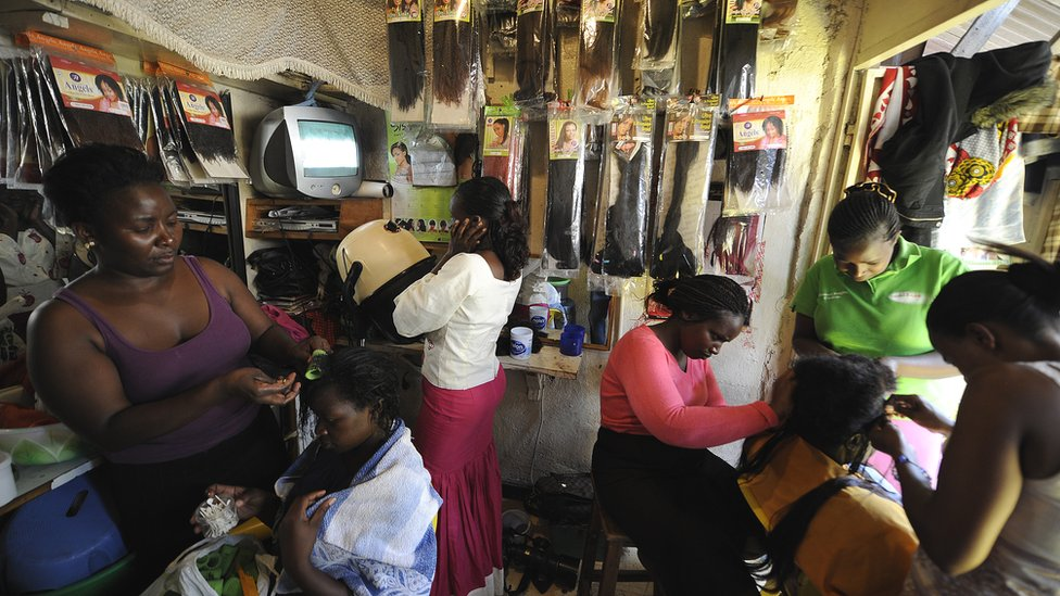 Kenyan hairdressers attending to clients at a salon in the capital Nairobi - archive shot