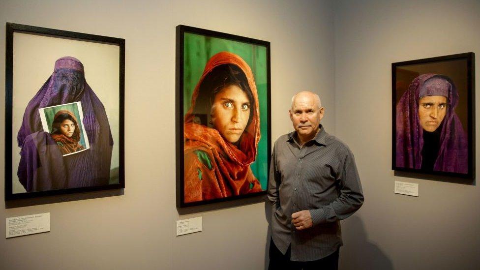 المصور الأمريكي ستيف ماكوري يقف بجانب صوره لشربات غولا، عام 2013