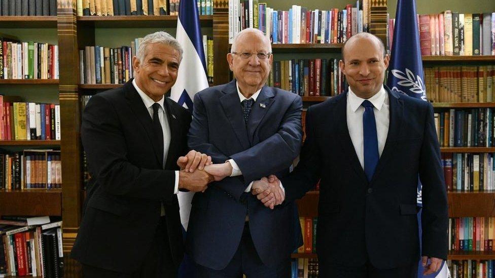 El presidente israelí Reuven Rivlin sosteniendo la mano del nuevo primer ministro Naftali Bennett (derecha) y del Ministro de Relaciones Exteriores Yair Lapid.