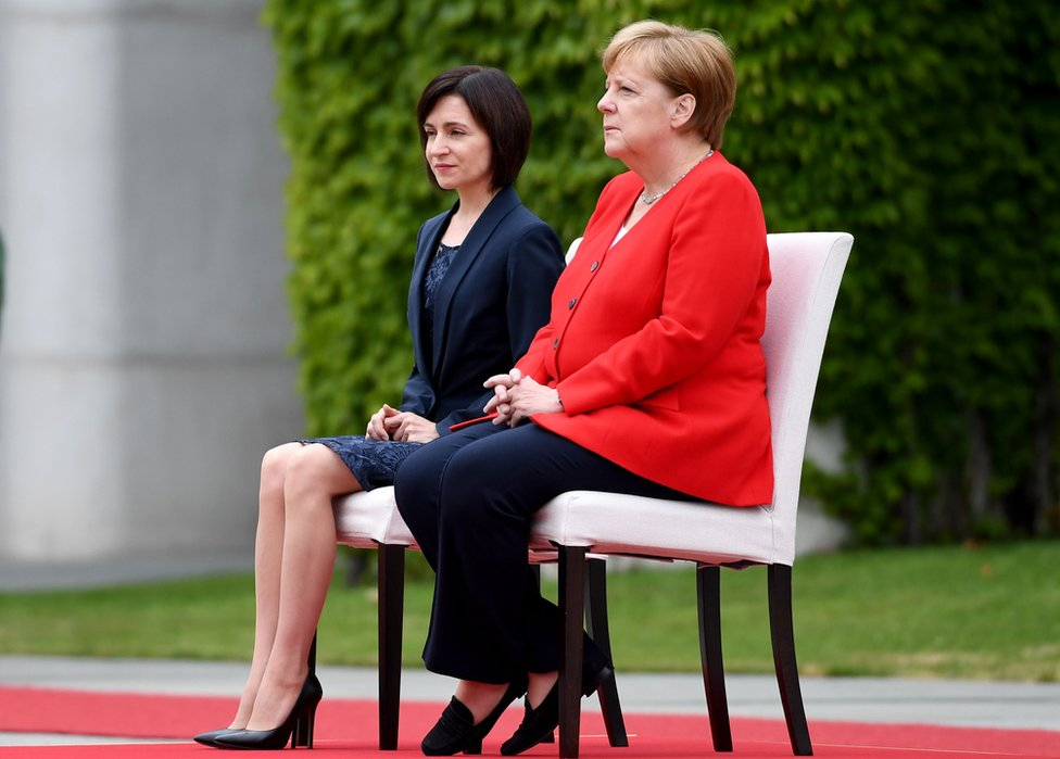 German Chancellor Angela Merkel (R) and Moldova's Prime Minister Maia Sandu sit as they listen to the national anthems during a welcoming ceremony with military honours at the Chancellery in Berlin on July 16, 2019