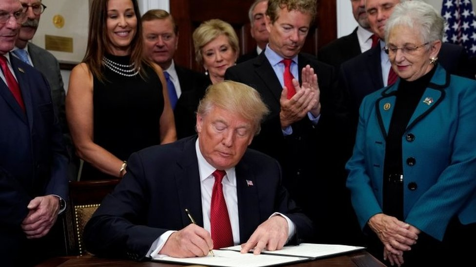 US President Donald Trump signs an executive order on healthcare at the White House.