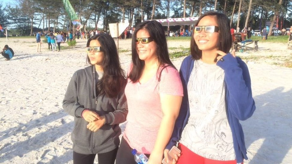 People watch the solar eclipse on Olivier beach, Belitung