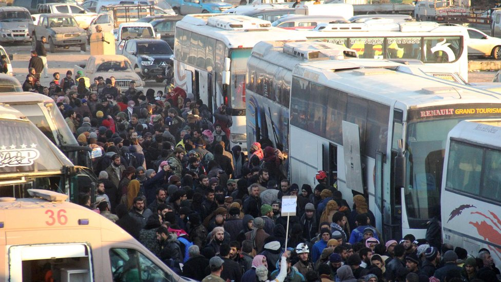 Syrians evacuated from rebel-held Aleppo arrive in Khan al-Assal on 19 December 2016