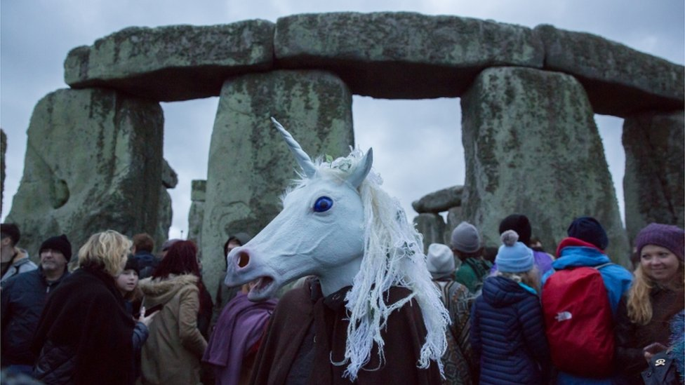 A unicorn head mask amid the crowds