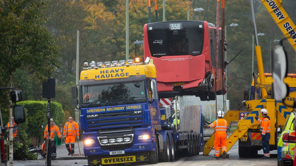 Bus being craned onto recovery truck
