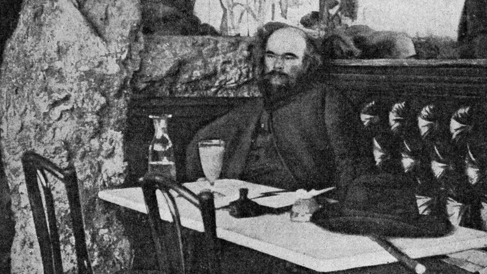 Paul Verlaine - portrait in front of a glass of absinthe at the Café Procope, Paris, France