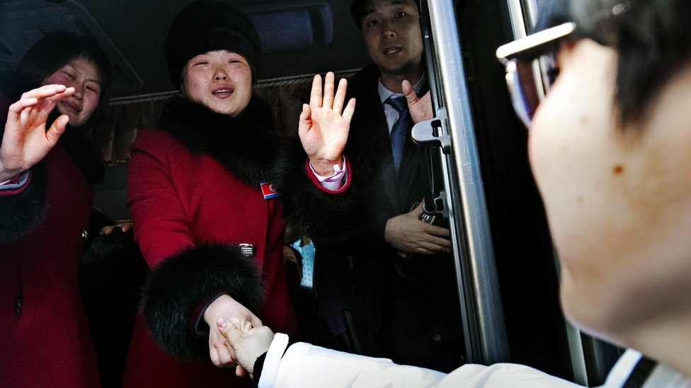 North Korean members of the joint inter-Korean women's ice hockey team bid a tearful farewell to their South Korean companions as they leave Gangneung Olympic Village