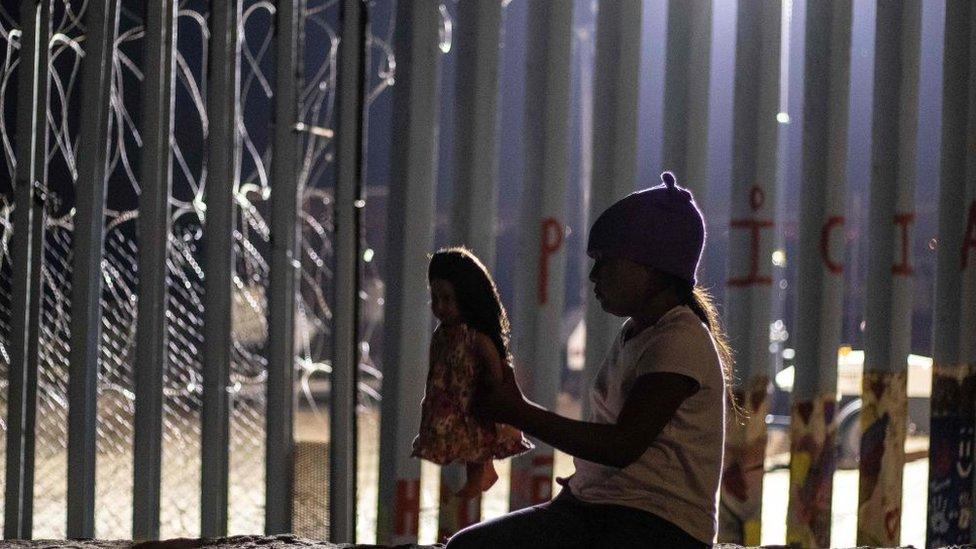 Niña migrante con muñeca al lado del muro