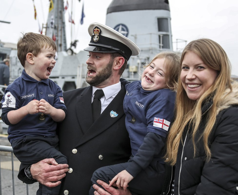 A sailor greets his family