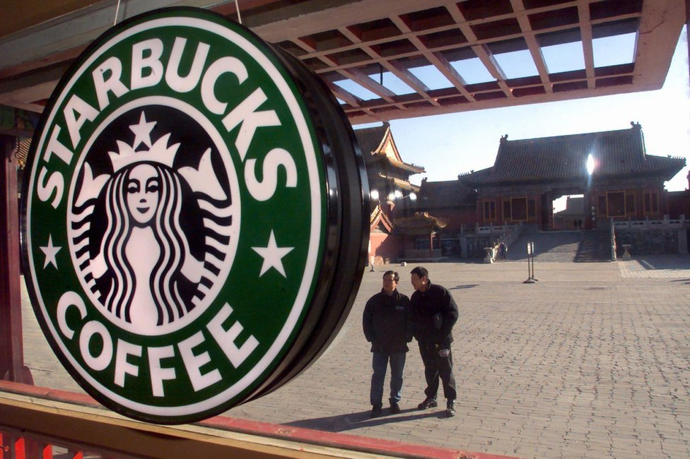 Two Chinese tourists look 10 November 2000 at a Starbucks coffee shop which has opened in the heart of Beijing's historic Forbidden City, once the exclusive preserve of China's emperors.