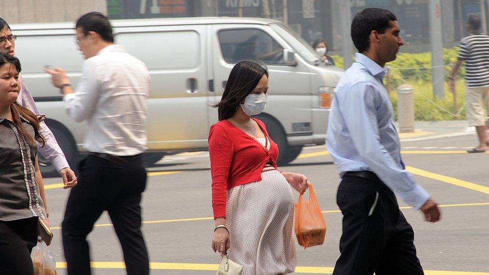 Mujer embarazada con máscara