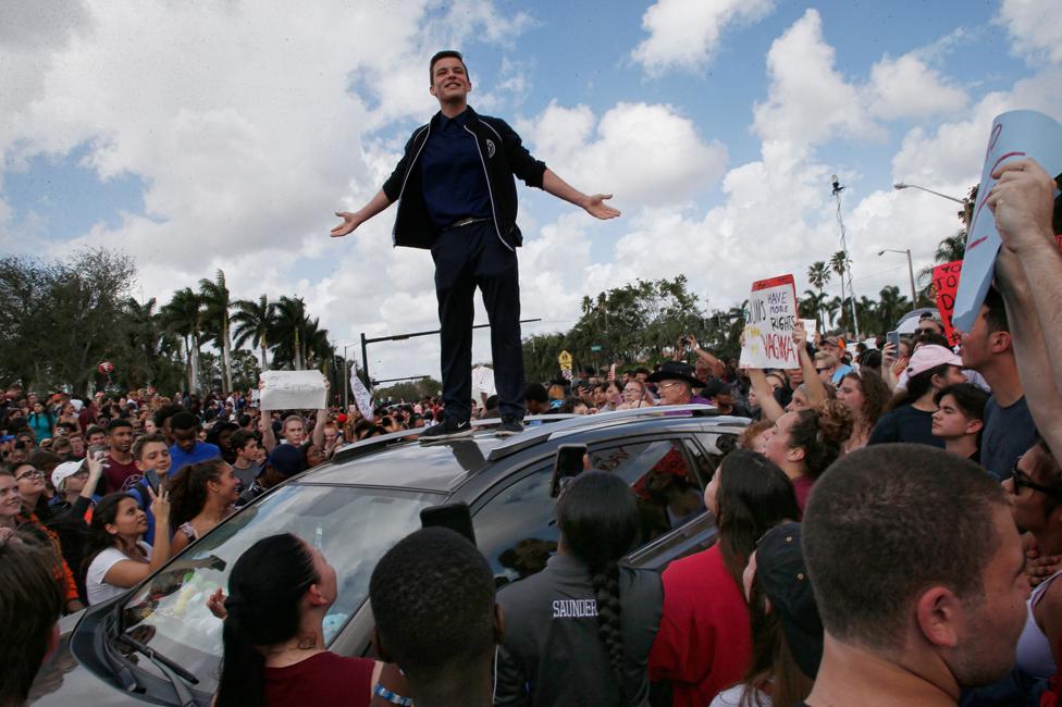 Cameron Kasky dando un discurso ante una multitud sobre un carro
