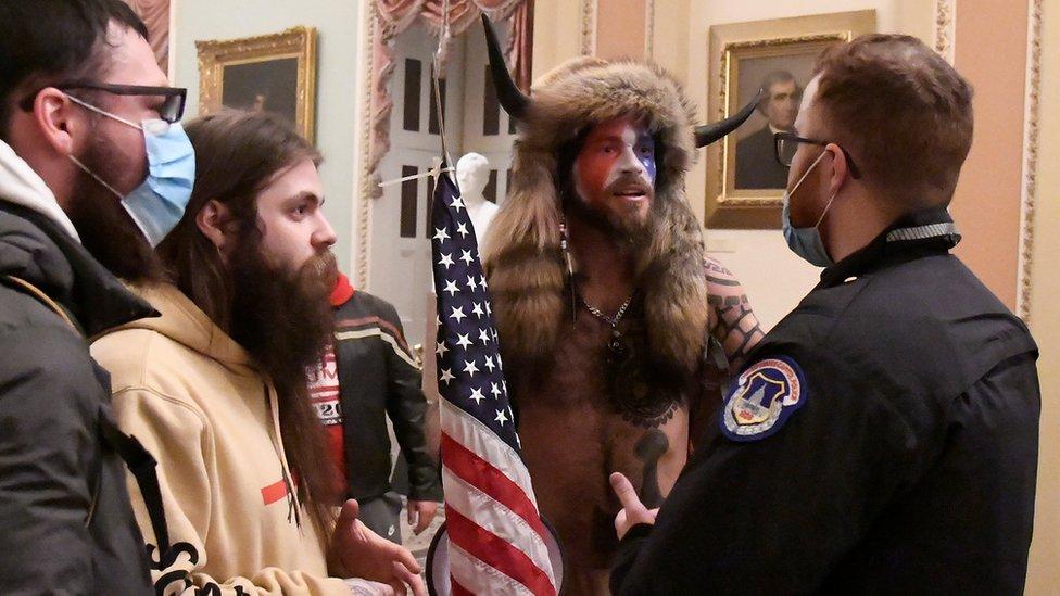 Un grupo de los asaltantes al Capitolio junto a un policía de la seguridad del edificio