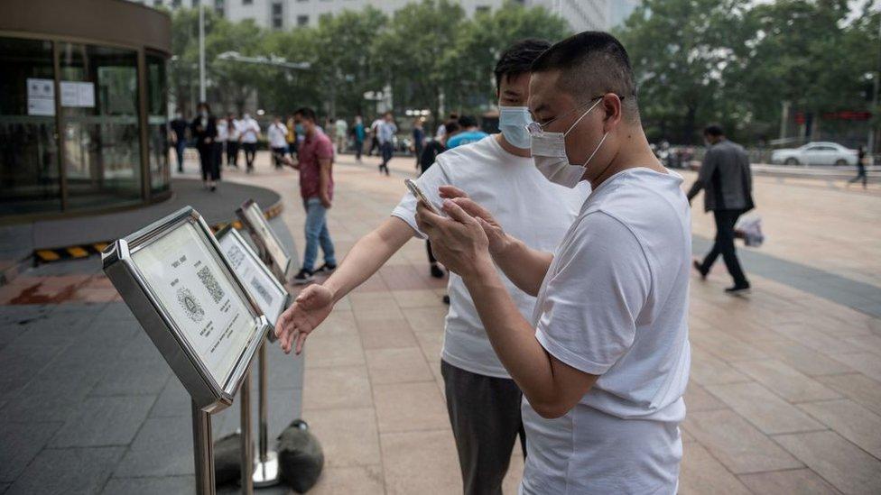 Hombres en China usando los códigos QR.