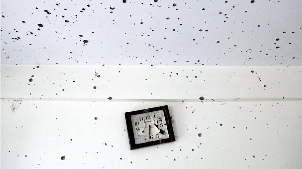 A damaged clock is seen inside a classroom after the attack at the university of Kabul