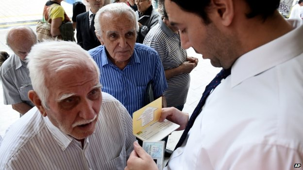 A bank employee checks the ID and bank booklet of a pensioner before enter a branch in the northern Greek port city of Thessaloniki, on 1 July