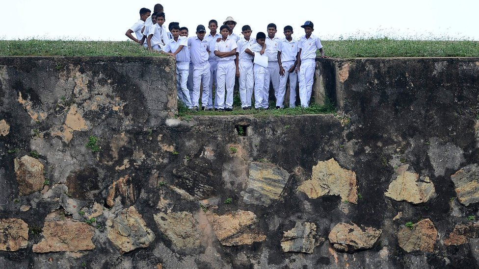 Sri Lankan schoolchildren stand on top of a 17th century Dutch fort overlooking Galle Stadium as they watch the fourth day of the opening Test match between Sri Lanka and Bangladesh in Galle (March 10 2017)