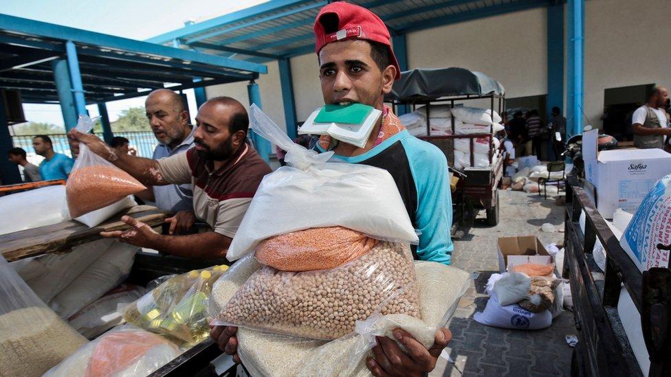 فلسطيني يحمل أكياسا من المواد الغذائية بمركز توزيع تابع للأونروا في غزة