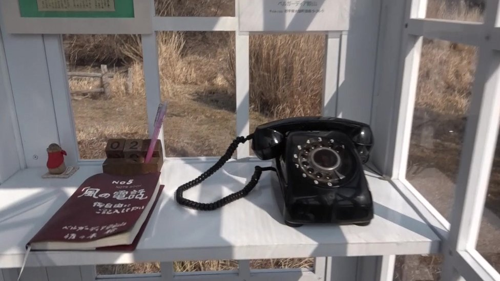 El teléfono negro dentro de la cabina.