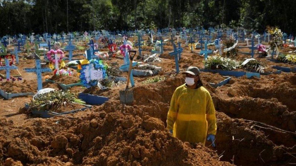 Coveiro de máscara em cemitério