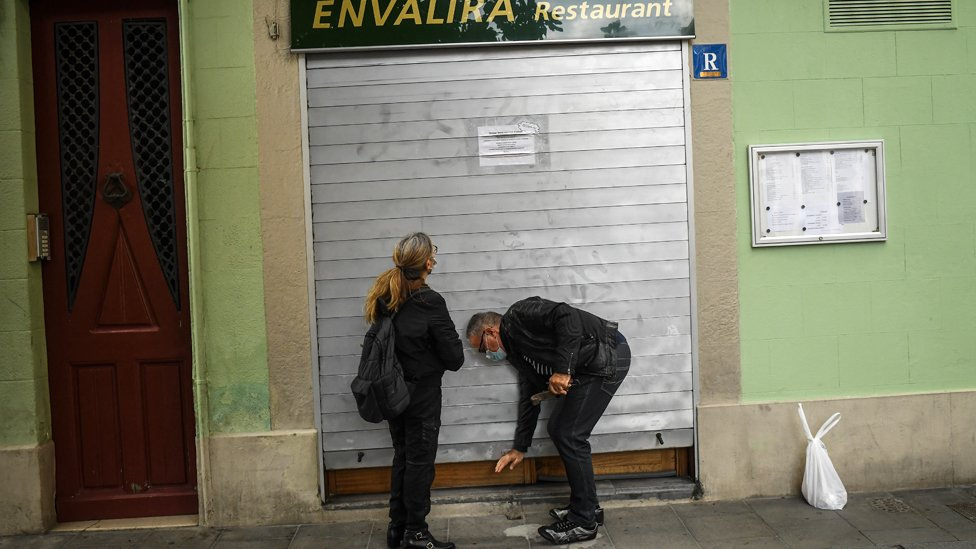 People close the shutter of a restaurant in Barcelona