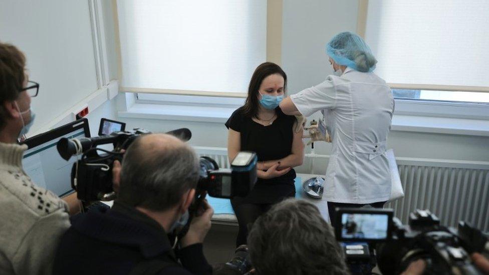 Mujer vacunándose frente a periodistas en Moscú.