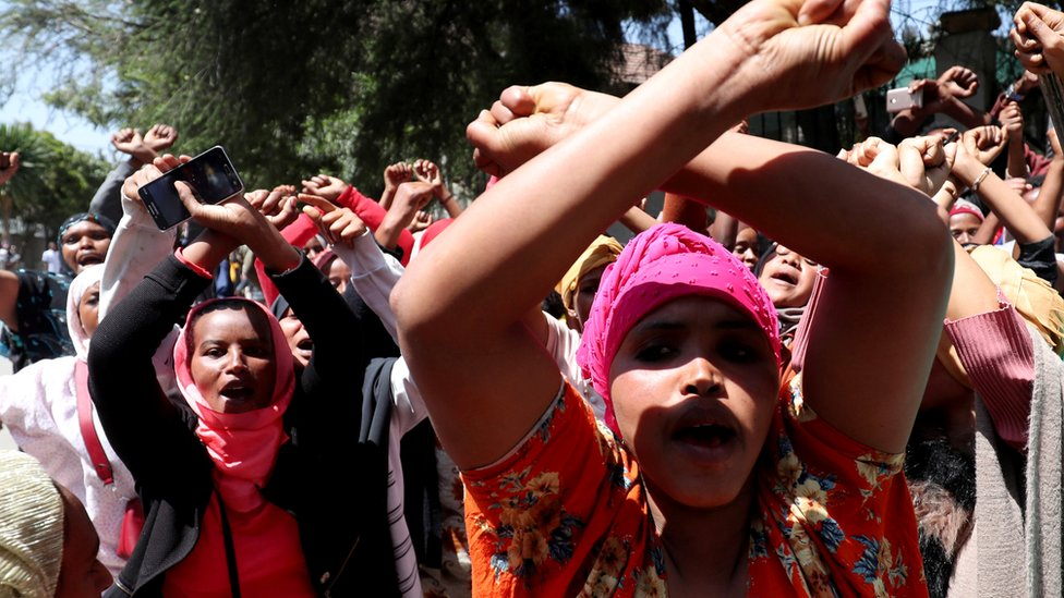 Women supporters show the Oromo protest gesture outside Jawar Mohammed's house