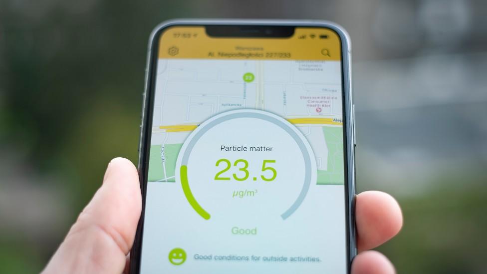 Celular que muestra en la pantalla niveles aceptables de material particulado PM 2,5