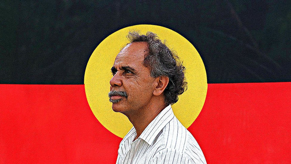 Side view of Harold Thomas in 1994 framed in the centre of an Aboriginal flag backdrop