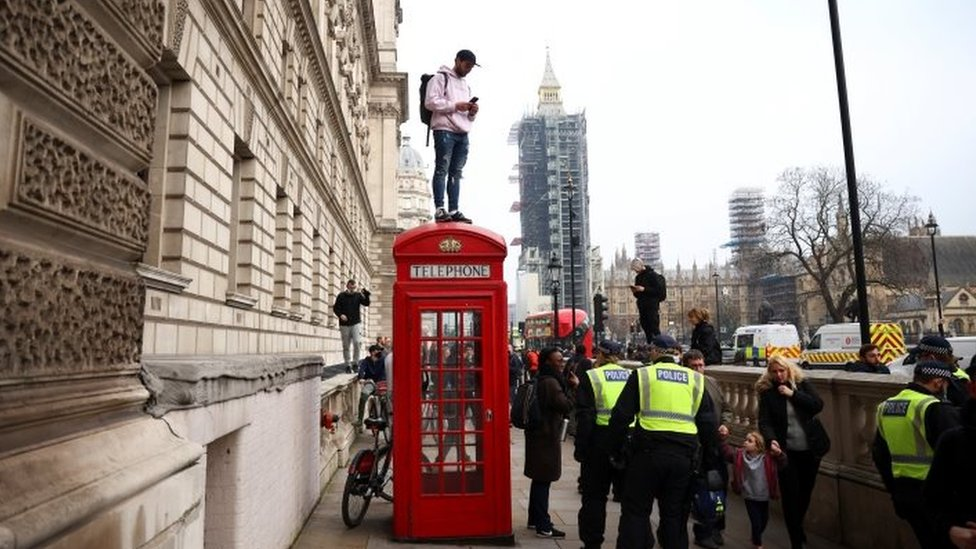 A protester standing on a telephone box in London