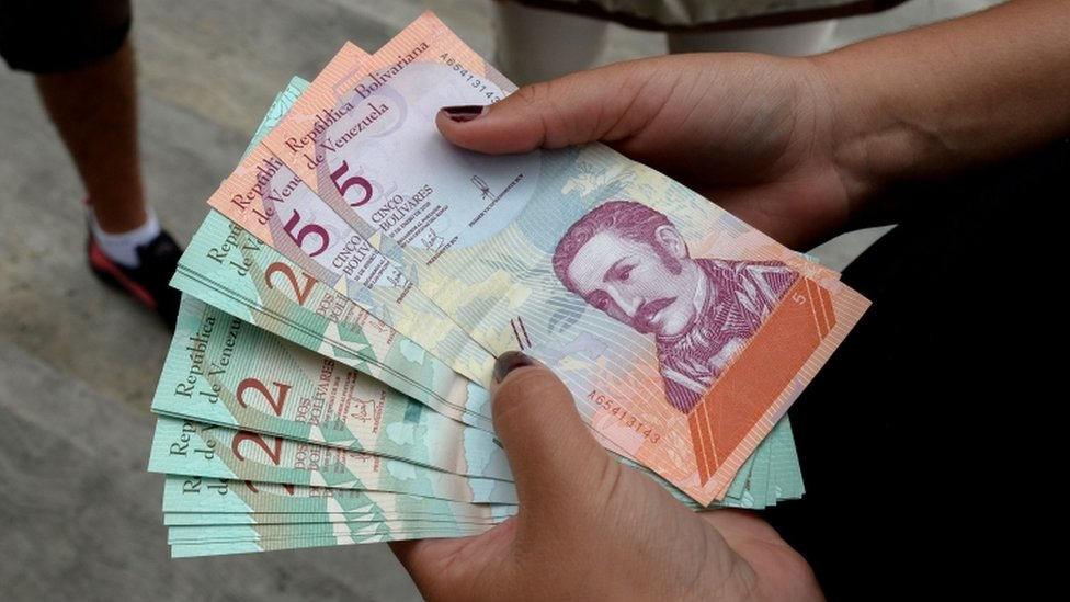 A woman holds new bolivar notes in downtown Caracas on 21 August, 2018.