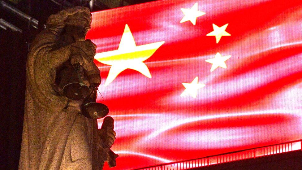 香港終審法院大樓樓頂正義女神像映照在一面投射在LED屏幕的中國國旗下(30/9/2019)