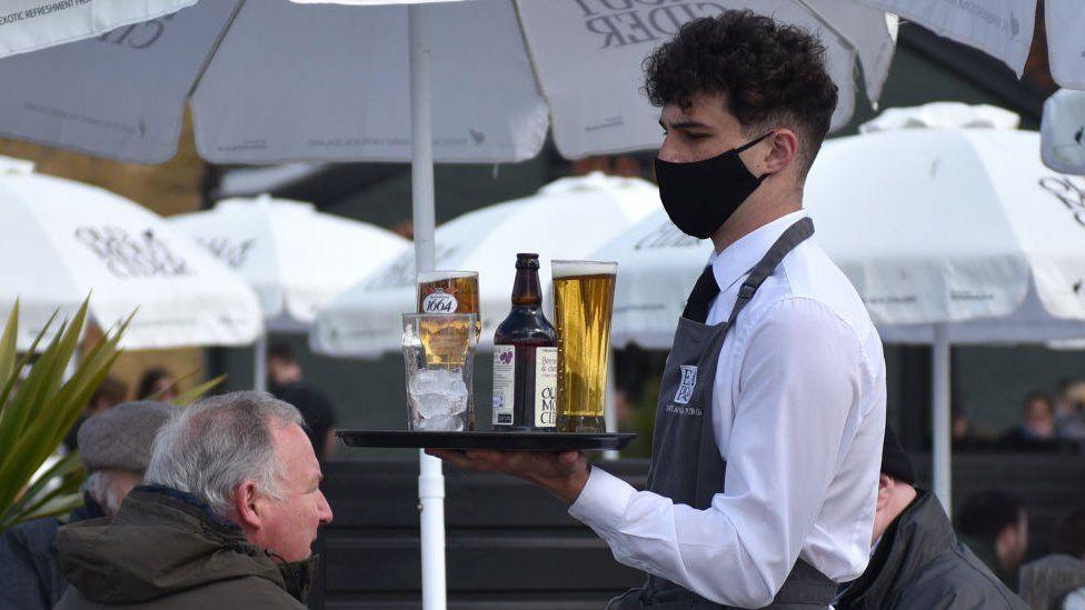 Garçom de máscara com bandeja com bebidas em restaurante