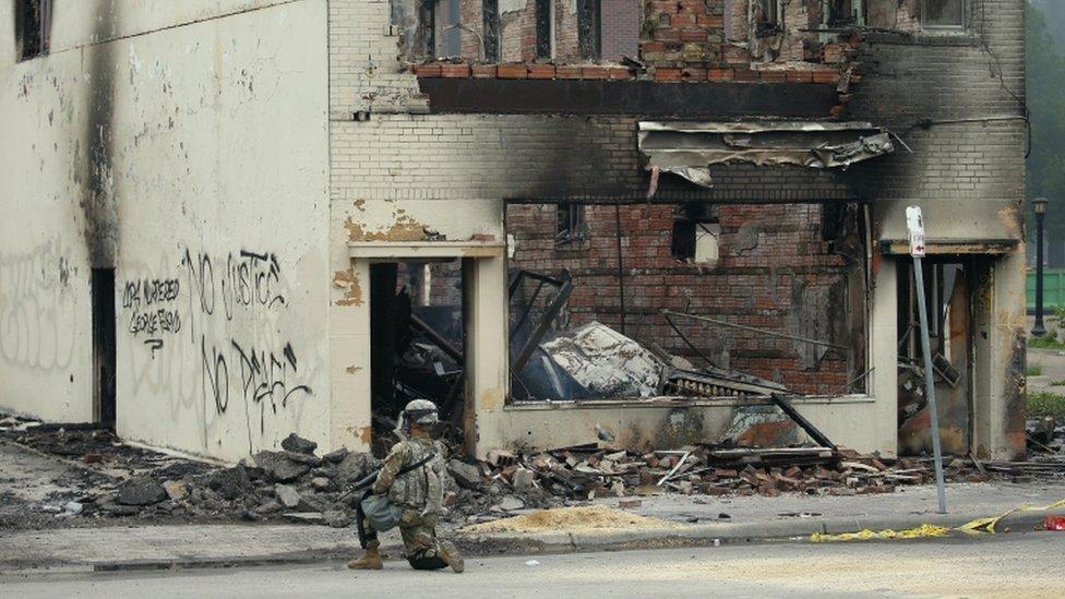 Un oficial de la Guardia Nacional frente a un edificio incendiado en Minneapolis.
