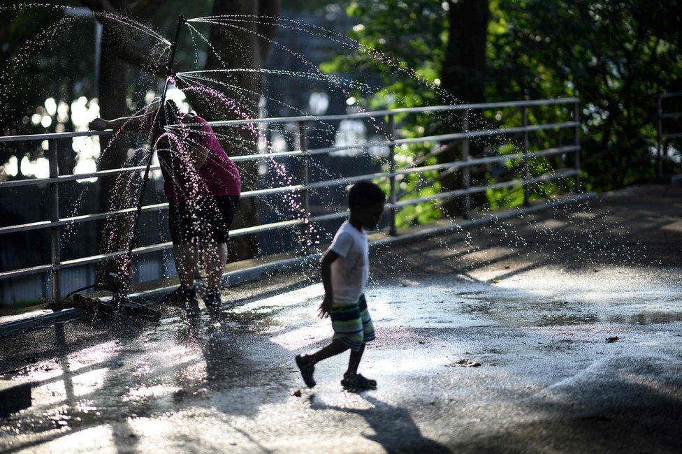 في مانهاتن، فتى آخر يلعب بمياه النافورة .
